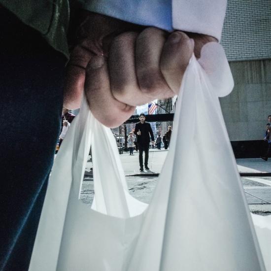Person mit Plastiktüte auf der Straße in Nahaufnahme
