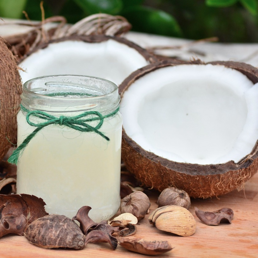 Halbe Kokosnuss mit einem Glas Kokosöl