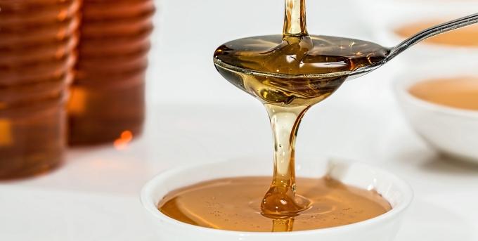 Honig fließt über einen Teelöffel