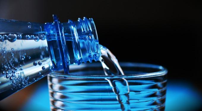 Aus einer Plastikflasche wird Mineralwasser in ein Glas gegossen