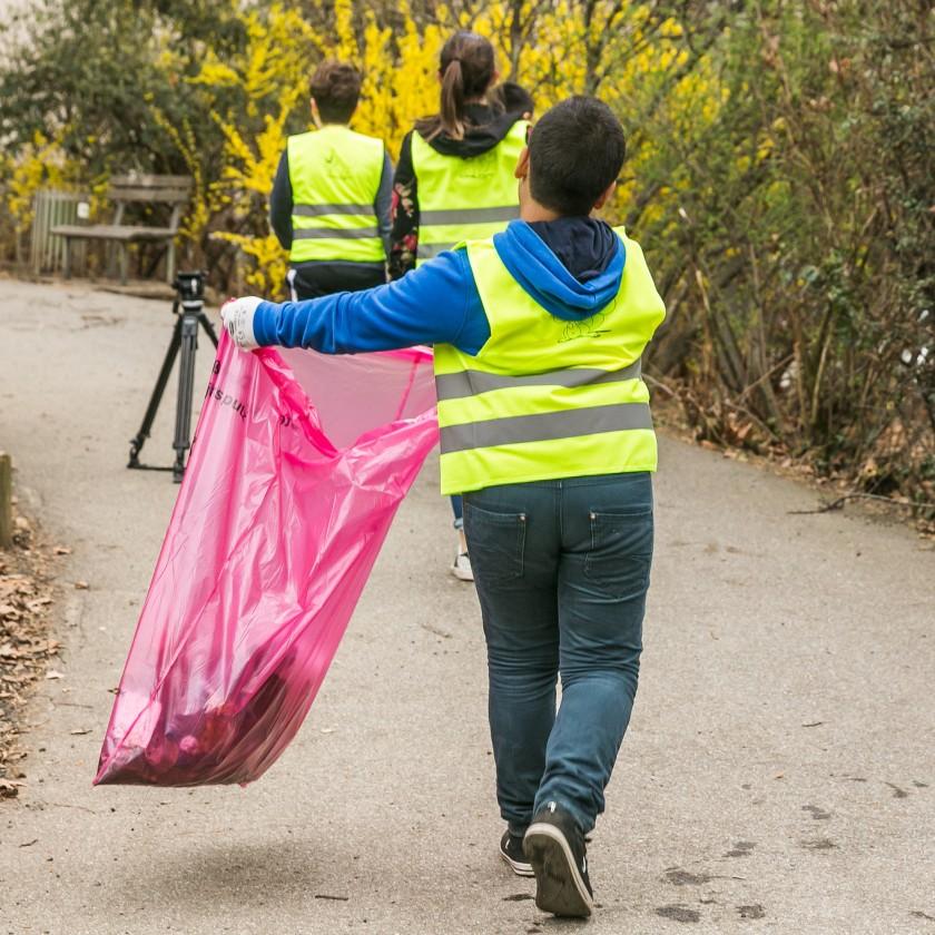 Kind mit Mülltüte und Warnweste auf der Straße